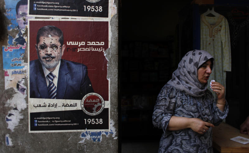"""An Egyptian female vendor stands at her shop next to a poster with a defaced pictures of presidential candidate Mohammed Morsi and Arabic that reads """"Mohammed Morsi, president for Egypt, revival is the will of the people,"""" in Cairo, Egypt Wednesday, June 20, 2012. The runoff pitted Mubarak's last prime minister Ahmed Shafiq against conservative Islamist Mohammed Morsi of the Muslim Brotherhood. The contest divided the country and their rival claims of victory could bring more of the turmoil that has rocked the country since Mubarak's ouster. (AP Photo/Nasser Nasser)"""