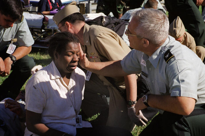 <p>Deputy chief of the Army Reserve, Col. Malcolm Bruce Westcott, comforts Pentagon employee Racquel Kelley while giving her medical aid outside the Pentagon in Washington on Tuesday, Sept. 11, 2001. (AP Photo/Will Morris)</p>