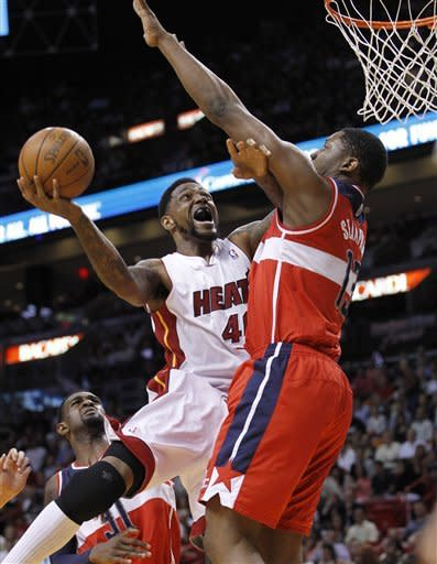 Miami Heat's Udonis Haslem (40) drives to the basket as Washington Wizards' forward Kevin Seraphin (13) defends in the first half of an NBA basketball game in Miami, Saturday, April 21, 2012. (AP Photo/Alan Diaz)