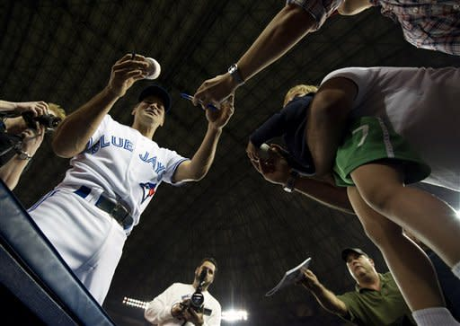 Toronto Blue Jays shortstop Omar Vizquel, left, signs autographs for fans before playing against the Minnesota Twins in a baseball game in Toronto, Wednesday, Oct. 3, 2012. Vizquel has said he plans to retire. (AP Photo/The Canadian Press, Nathan Denette)