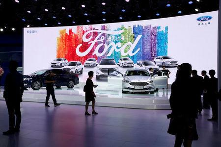 FILE PHOTO: Visitors look at Ford models at Auto Guangzhou in Guangzhou