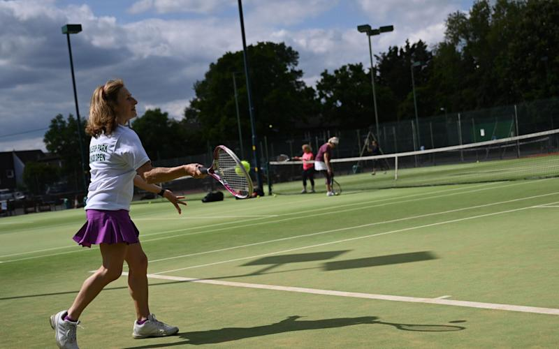 Players enjoy a tennis match at Oakleigh Park Lawn Tennis & Squash Club in London, - SHUTTERSTOCK