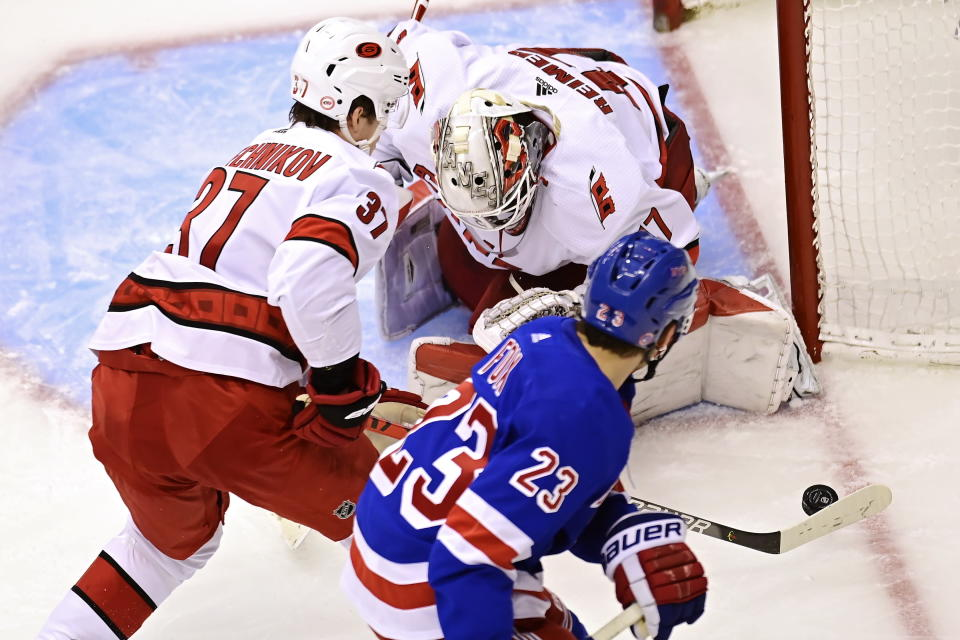 Carolina Hurricanes' goaltender James Reimer (47) looks for the puck as Hurricanes' Andrei Svechnikov (37) and New York Rangers' Adam Fox (23) chase during second period NHL Eastern Conference Stanley Cup playoff action in Toronto on Tuesday, Aug. 4, 2020. (Frank Gunn/The Canadian Press via AP)