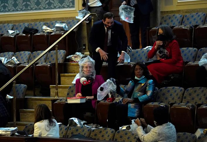 """People put on gas masks while sheltering in the House Chamber.<span class=""""copyright"""">Drew Angerer—Getty Images</span>"""