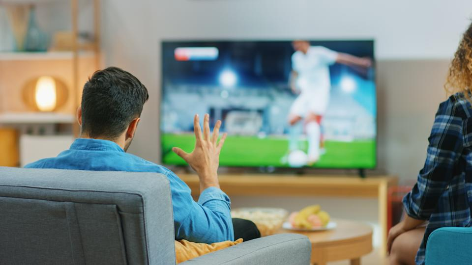 At Home Young Couple Watches Tense Moment of Soccer Match on TV, They Worry, Guy Trying to be Patient and Aggressively Showing Palm. Back View Shot.