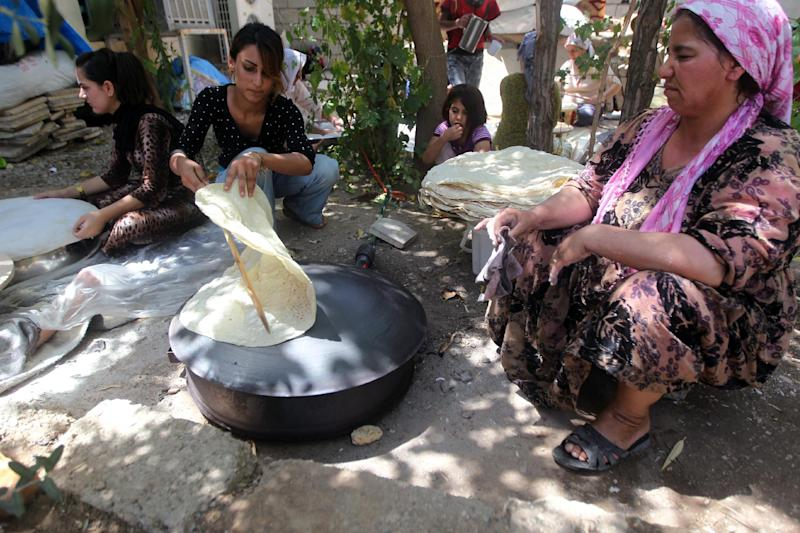 Kurdish women bake bread on a domed metal griddle for baking traditional flat bread, known locally in the region as the saj, at the mosque where they sought refuge in the village of Hajyawa, Iraq's Sulaimaniyah district, on August 21, 2014
