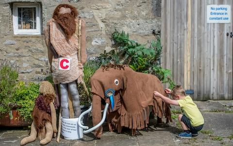 """The residents of Kettlewell have put Donald Trump in the stocks. Not the president himself but, perhaps fittingly, a straw-man version. He is one of 100 scarecrows on display around this pretty village in the Yorkshire Dales this past week. The Kettlewell Scarecrow Festival is said to be the biggest of its kind in the country – more than 15,000 people will have travelled from around the UK to admire the locals' handiwork – all 350 villagers work for months to ensure each year is a triumph. Without the school, Kettlewell would become a village of retirement and holiday homesMaggie Walker The real success, though, is how it has changed the fortunes of Kettlewell. While many of Britain's rural communities face shrinking services and an exodus of the young, Kettlewell has bucked the trend. The village has three pubs, a post office, a shop, a school, a youth hostel and a very lively village hall. And it is the money raised from the annual scarecrow festival that has ensured their continued survival. Nicky Fairweather moved to the village four years ago because there was a school for her son Jake, seven, to attend (it will have 31 pupils this September). Outside their front door is a medieval crusader, which Nicky made at a workshop a few weeks ago in the village hall, bonding with other locals while stuffing hay into tights and coming up with wildly creative concepts – woolly mammoth, anyone? Donald Trump in the stocks in the centre of Kettlewell Credit: Charlotte Graham """"Everyone has to come together to make it a success,"""" says Nicky, 45. """"Financially, it's been very important because it's a fragile situation – if you lose the school, you lose families, while others won't want to move to the village."""" The first festival took place in 1994 after a villager attended a similar event in France. Now, around 400 drivers pay £3 for parking in a local field and roughly 50 coaches wind up the road for one mad August week. Last year the festival raised £8,000 each for the school,"""