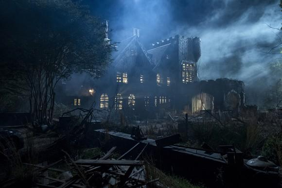 A creepy, old Gothic house on a cloudy moonlit night.