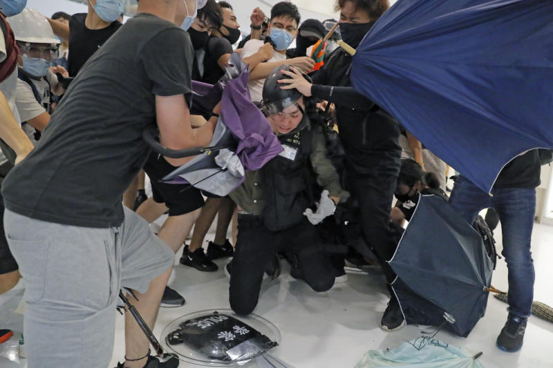 In this Sunday, July 14, 2019, photo, a policeman is attacked by protesters inside a shopping mall in Sha Tin District in Hong Kong9. Police in Hong Kong have fought with protesters as they broke up a demonstration by thousands of people demanding the resignation of the Chinese territory's chief executive and an investigation into complaints of police violence. (AP Photo/Kin Cheung)