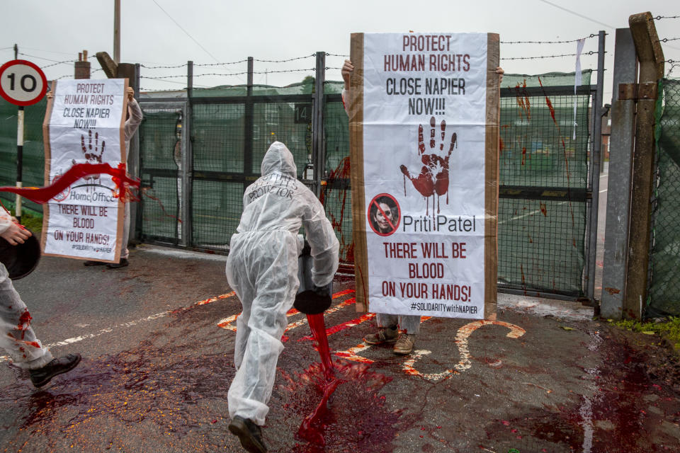 Activists take radical action throwing buckets of fake blood at Napier Barracks to highlight human rights violations on the 28th of January 2021 in Folkestone, United Kingdom. Activists dressed in white suits and masks, threw the fake blood through the gates of Napier Barracks to send a clear message to Priti Patel and the Home office to close Napier camp or there will be blood on your hands Following ongoing concerns over the poor living conditions at Napier barracks, and the failures in handling the inevitable Covid-19 outbreak onsite, pressure has been mounting on the Home Office to close the camp. (photo by Andrew Aitchison / In pictures via Getty Images)