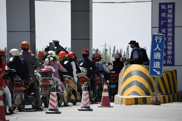 Observers say racial profiling is prevalent in China's western Xinjiang region, with Han Chinese often waved through police checkpoints while Uighurs are stopped (AFP Photo/GREG BAKER)