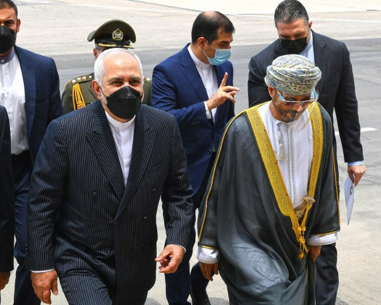 Iranian Foreign Minister Mohammad Javad Zarif (L) arrives in the Omani capital Muscat on April 28, 2021 as part of a regional tour