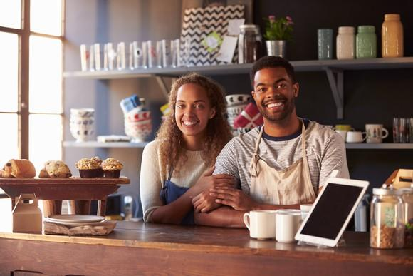 Couple standing behind coffee shop counter