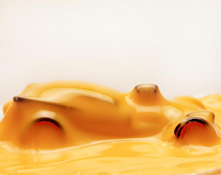 A matchbox car covered in a thick, melty layer of American cheese