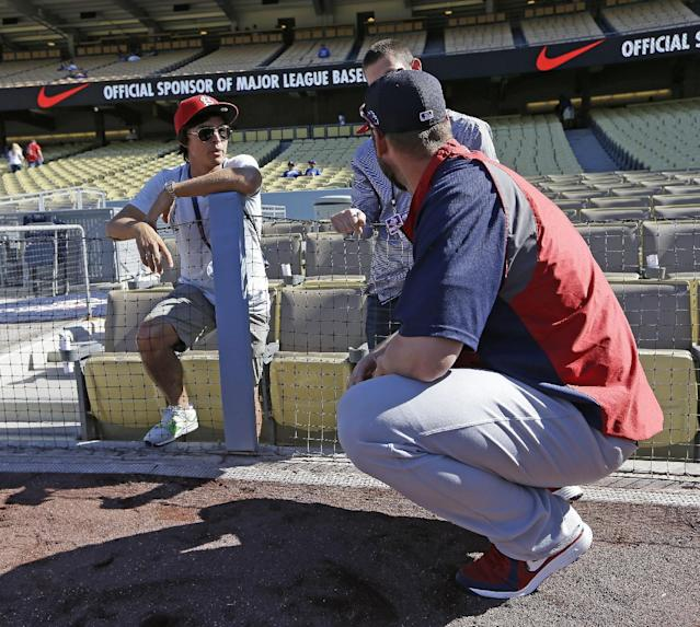 Golfer Rickie Fowler, left, speaks with St. Louis Cardinals' Chris Carpenter during batting practice before to Game 4 of the National League baseball championship series against the Los Angeles Dodgers, Tuesday, Oct. 15, 2013, in Los Angeles. (AP Photo/David J. Phillip)
