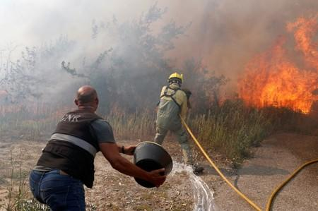 Firefighters help to put out a forest fire near the village of Vila de Rei,