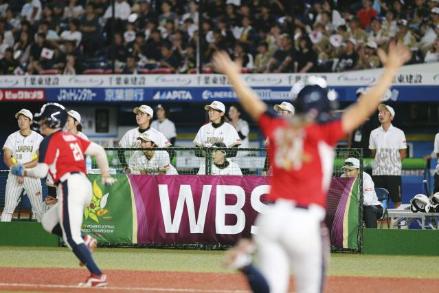 Japan's players, in white jersey, react to a walk-off loss as U.S. team members, in red jersey, celebrate during Women's Softball World Championship game Saturday Aug. 11, 2018 in Makuhari, east of Tokyo. United States to a 4-3 win over Japan and into the final of the women's world softball championship. (Kyodo News via AP)