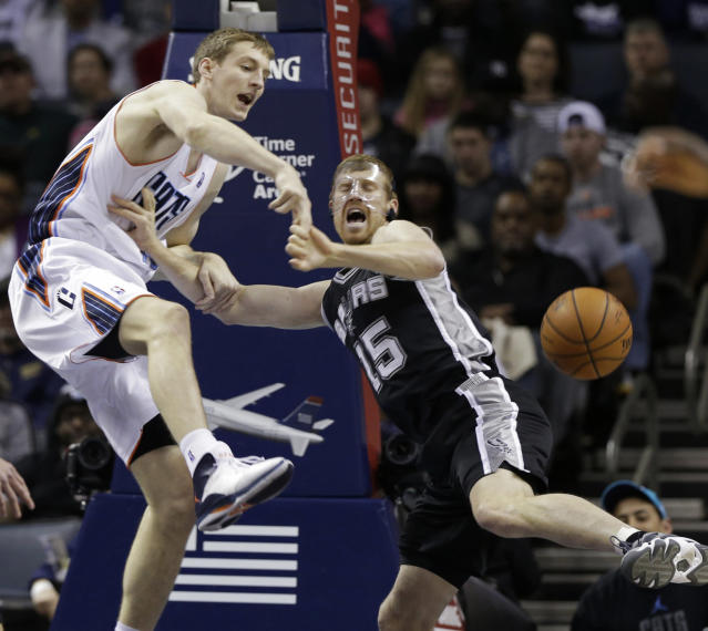 Charlotte Bobcats' Cody Zeller, left, and San Antonio Spurs' Matt Bonner, right, battle for a rebound during the first half of an NBA basketball game in Charlotte, N.C., Saturday, Feb. 8, 2014. (AP Photo/Chuck Burton)