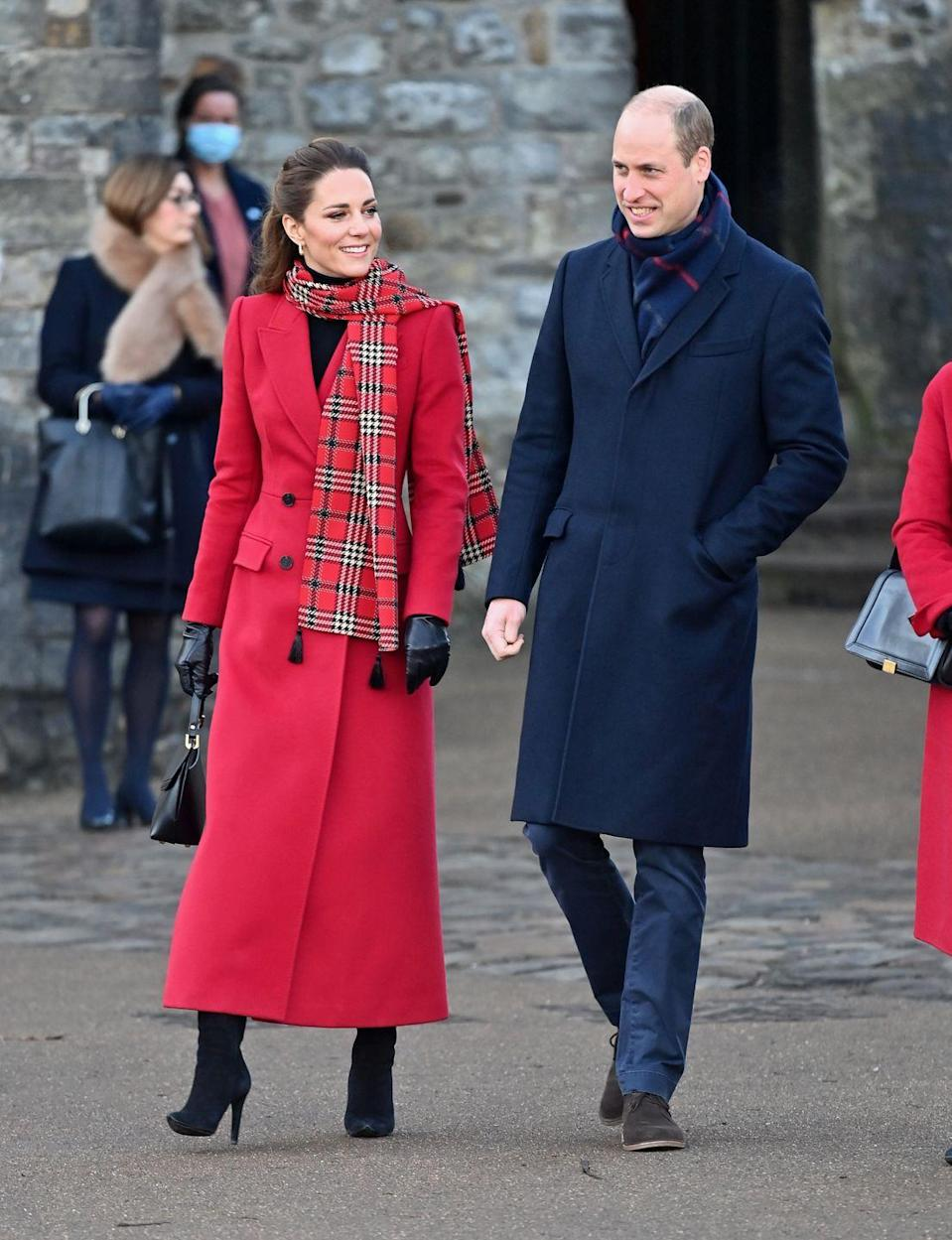 <p>While on their royal train tour to thank transport workers in London, the duchess wore a festive red wool coat with a plaid scarf and black suede boots.</p>