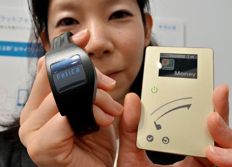 Sony's prototype model of a smart card with a NFC chip (R) which has a LCD display enabling users to check the account balance, electronic coupon and other electronic information and a wrist watch shaped device, seen in Tokyo, on July 17, 2014 (AFP Photo/Yoshikazu Tsuno)