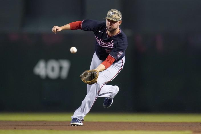Washington Nationals second baseman Jordy Mercer reaches out to field a grounder hit by Arizona Diamondbacks' David Peralta before throwing to first base for an out during the first inning of a baseball game Sunday, May 16, 2021, in Phoenix. (AP Photo/Ross D. Franklin)