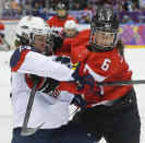 Michelle Picard of the United States (23) gets tangled up with Rebecca Johnston of Canada (6) during the first period of the women's gold medal ice hockey game at the 2014 Winter Olympics, Thursday, Feb. 20, 2014, in Sochi, Russia. (AP Photo/Matt Slocum)