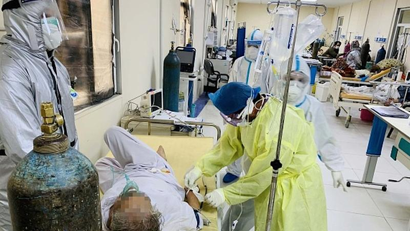 Afghan doctors help patients to breath through oxygen mask in Afghan-Japan special hospital for Covid-19 patients in Kabul, Afghanistan