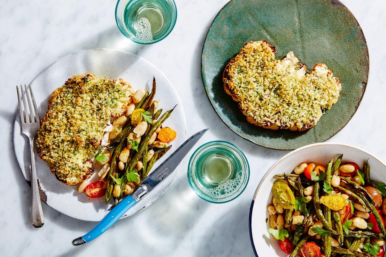 """An herbed garlic oil does double duty in this sheet-pan dinner. First, it's mixed with Parmesan and panko to create a crispy crust for the cauliflower. Then, it's tossed with cherry tomatoes and beans for a zesty side dish. <a href=""""https://www.epicurious.com/recipes/food/views/herb-crusted-cauliflower-steaks-with-beans-and-tomatoes?mbid=synd_yahoo_rss"""">See recipe.</a>"""