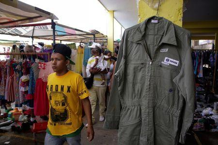 A boy walks past a PDVSA's overall for sale at a market in Maracaibo, Venezuela September 11, 2016. REUTERS/Jesus Contreras