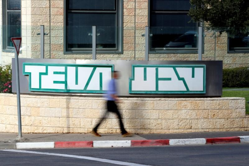 FILE PHOTO: A man walks past the logo of Teva Pharmaceutical Industries at their plant in Jerusalem