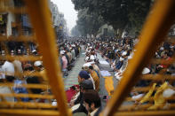 Muslim protesters are seen through a police barricade as they pray on a road near the historic Red Fort in New Delhi, India, Friday, Dec. 20, 2019. Police banned public gatherings in parts of the Indian capital and other cities for a third day Friday and cut internet services to try to stop growing protests against a new citizenship law that have so far left more than 10 people dead and more than 4,000 others detained. (AP Photo/Altaf Qadri)