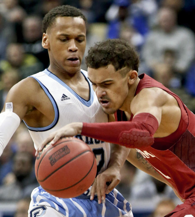 Oklahoma's Trae Young, right, tries to get past Rhode Island's Fatts Russell during the first half of an NCAA men's college basketball tournament first-round game, Thursday, March 15, 2018, in Pittsburgh. (AP Photo/Keith Srakocic)