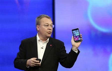 "Stephen Elop, vice president of Nokia, gestures while introducing the Nokia Lumia 930 mobile phone during Microsoft's ""build"" conference in San Francisco"