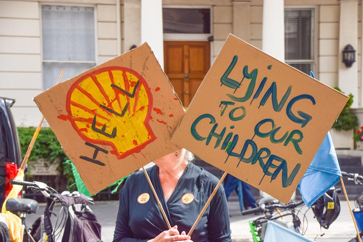 A demonstrator holds anti-Shell placards outside the Science Museum during the anti-Shell sponsorship protest.