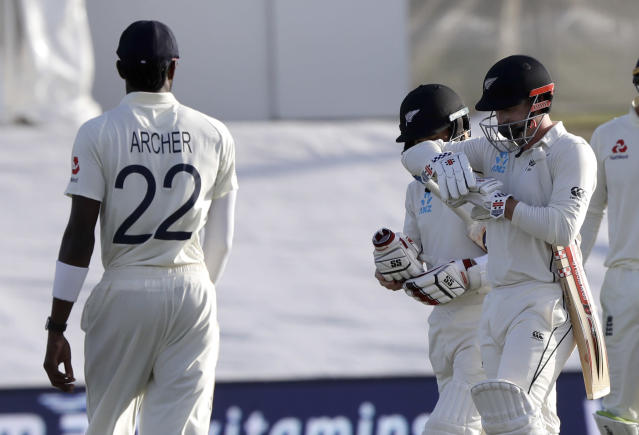 England's Jofra Archer, left, watches as not out batsman New Zealand's Henry Nicholls, right, and BJ Watling walk from the field at the close of play during play on day two of the first cricket test between England and New Zealand at Bay Oval in Mount Maunganui, New Zealand, Friday, Nov. 22, 2019. (AP Photo/Mark Baker)