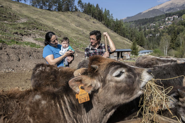 In this image take on Thursday, April 23, 2020 Stefano Gusmini, 43, right, looks at his wife Alice Piccardi, 37, holding their five month old son Danilo, at their farm 'Fattoria della Felicita'' (Farm of Happiness), which hosts also a restaurant and summer camps, in Onore, near Bergamo, northern Italy. In her afternoons she volunteers at the doctor's dormitory at a field hospital in Bergamo. (AP Photo/Luca Bruno)