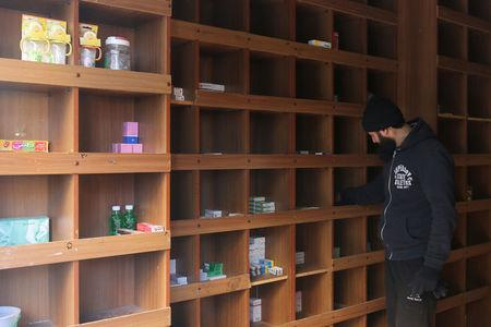 A pharmacist inspects low medical supplies inside a pharmacy in a rebel-held besieged area in Aleppo, Syria December 2, 2016. REUTERS/Abdalrhman Ismail