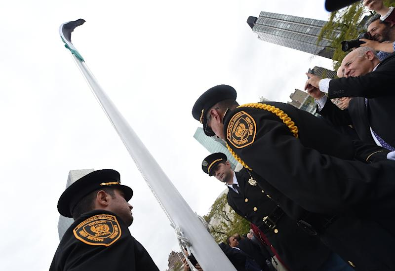Media and UN Honour Guard members gather during the Palestinian flag raising ceremony at the UN in New York on September 30, 2015 (AFP Photo/Timothy A. Clary)
