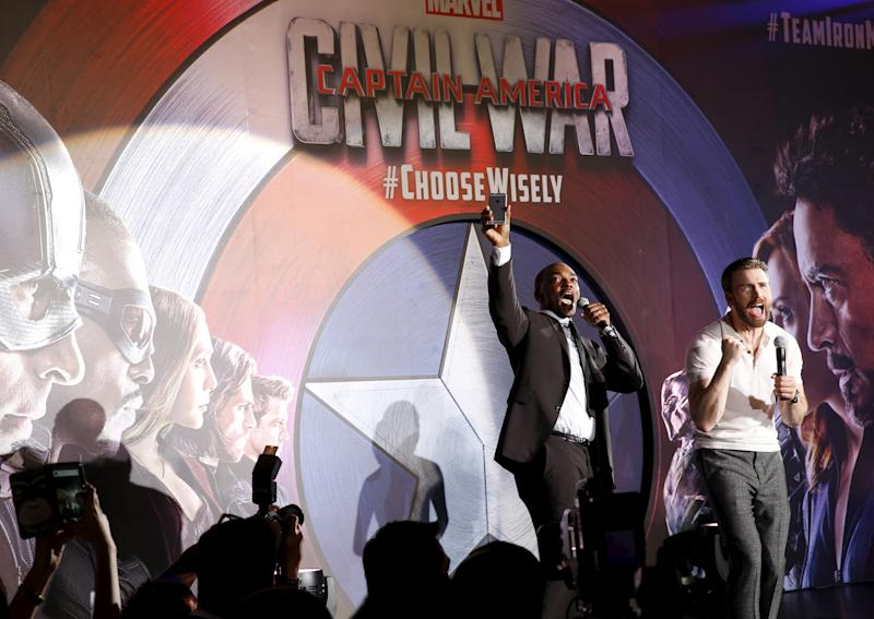 "Actors Chris Evans and Anthony Mackie (L) greet fans during a blue carpet event for the movie ""Captain America: Civil War"" in Singapore, April 21, 2016. REUTERS/Edgar Su"