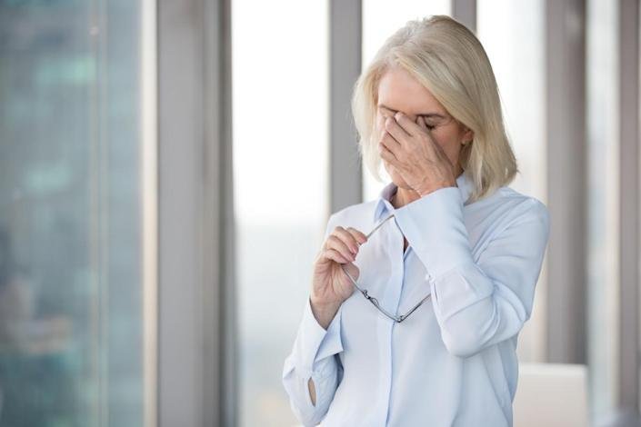 Tired mature woman take off glasses suffering from headache