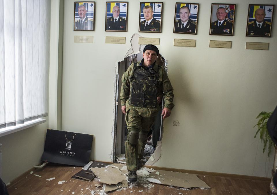 Crimean self-defense forces member walks in the Ukrainian navy headquarters in Sevastopol, Crimea, Wednesday, March 19, 2014. Crimea's self-defense forces on Wednesday stormed the Ukrainian navy headquarters in the Black Sea port of Sevastopol, taking possession without resistance a day after Russia signed a treaty with local authorities to annex the region. (AP Photo/Andrew Lubimov)