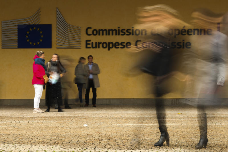 People walk past European Commission headquarters in Brussels, Friday, Oct. 4, 2019. A document read aloud in a Scottish court says British Prime Minister Boris Johnson would seek an extension to the Oct. 31 Brexit deadline if no withdrawal deal with the European Union is reached by mid-October. (AP Photo/Francisco Seco)