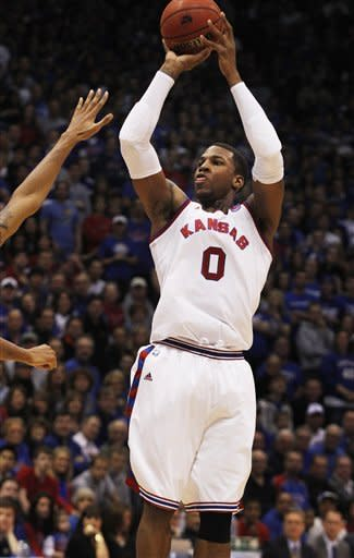 Kansas forward Thomas Robinson (0) shoots a three-point basket during the second half of an NCAA college basketball game against Oklahoma State in Lawrence, Kan., Saturday, Feb. 11, 2012. Robinson scored 24 points in the game. Kansas defeated Oklahoma State 81-66. (AP Photo/Orlin Wagner)