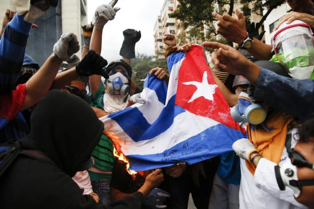 Anti-government protesters set fire to a Cuban flag during a protest against Nicolas Maduro's government in Caracas March 7, 2014. Latin American foreign ministers will meet next week to discuss the unrest in Venezuela that has left at least 20 dead and convulsed the South American OPEC nation, diplomatic sources said on Friday. REUTERS/Carlos Garcia Rawlins (VENEZUELA - Tags: POLITICS CIVIL UNREST)