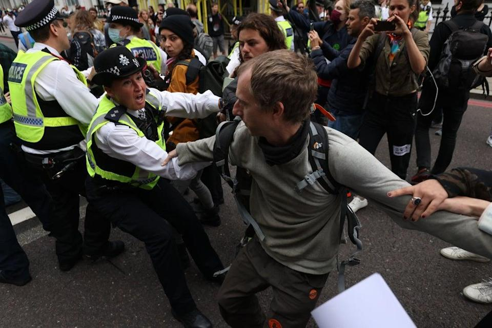 A police office tussles with a demonstrator on the A4 outside the Natural History Museum  (PA)