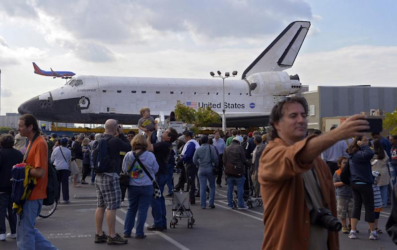 """Spectators gather around the Space Shuttle Endeavour before it is moved along city streets, Friday, Oct.12, 2012, in Los Angeles. Endeavour's two-day, 12-mile road trip to the California Science Center, where it will be put on display, kicked off early Friday. Rolled on a 160-wheeled carrier, it left from a hangar at the Los Angeles International Airport, passing diamond-shaped """"Shuttle Xing"""" signs, and reached city streets about two hours later. (AP Photo/Mark J. Terrill)"""