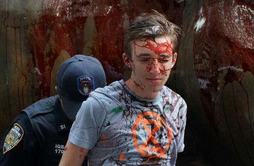 Protestors covered in fake blood are arrested by the NYPD around the Wall Street Bull during an ?Extinction Rebellion? demonstration in New York