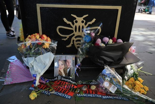 Flowers and a picture of Chloe Rutherford and Liam Curry, who were killed in the Manchester Arena attack, left against a Tree of Hope in Manchester (Peter Byrne/PA)