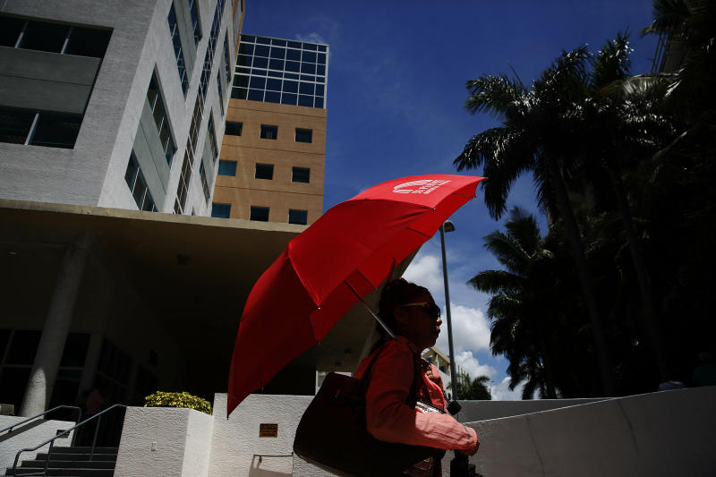 In this June 12, 2019, photo, a woman walks in front of immigration court in Miami. The Trump administration has appointed more than 4 in 10 of the country's sitting immigration judges in a hiring surge that comes as U.S. authorities seek to crack down on immigration. (AP Photo/Brynn Anderson)