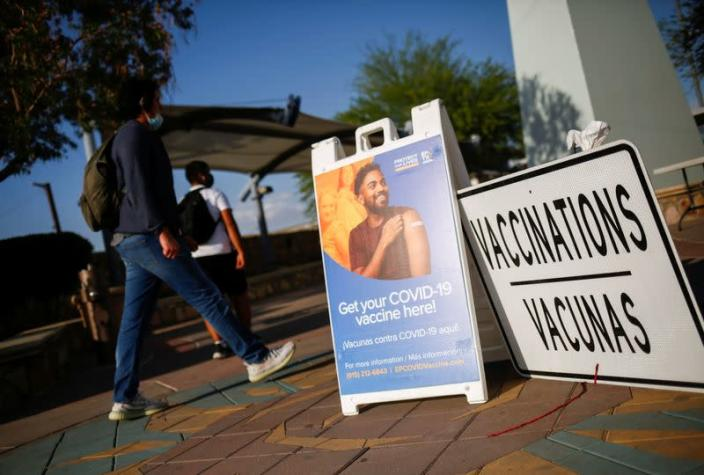People walk past at a vaccination centre for the coronavirus disease (COVID-19), in El Paso